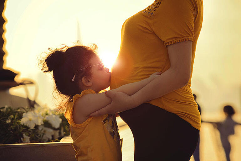 Little girl kissing mums pregnant belly