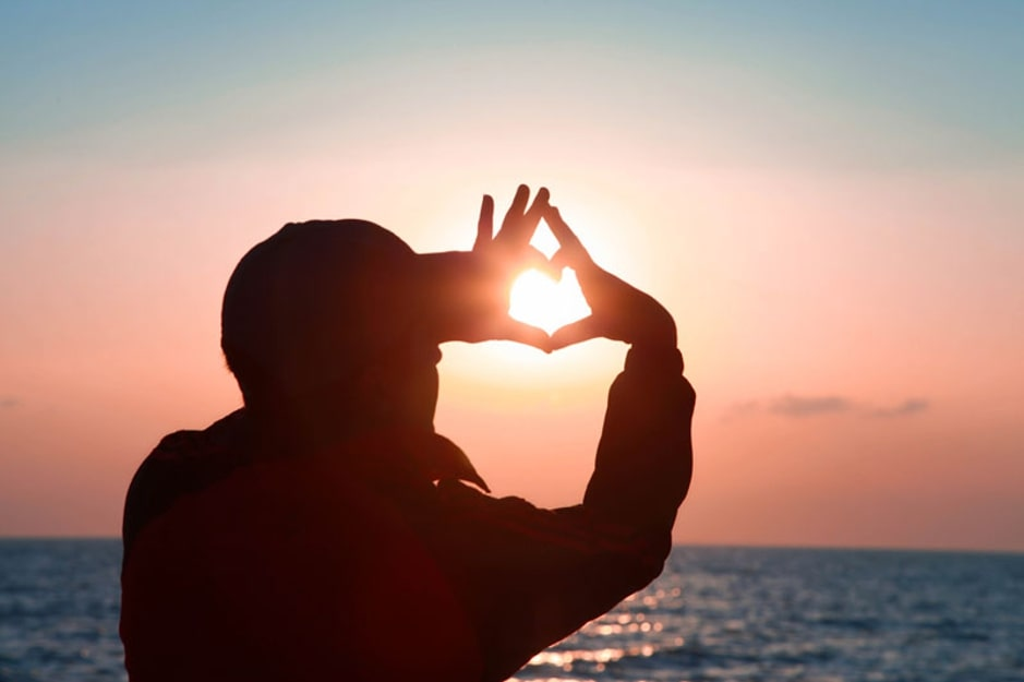 Person holding up a heart with their hand and looking at the sun