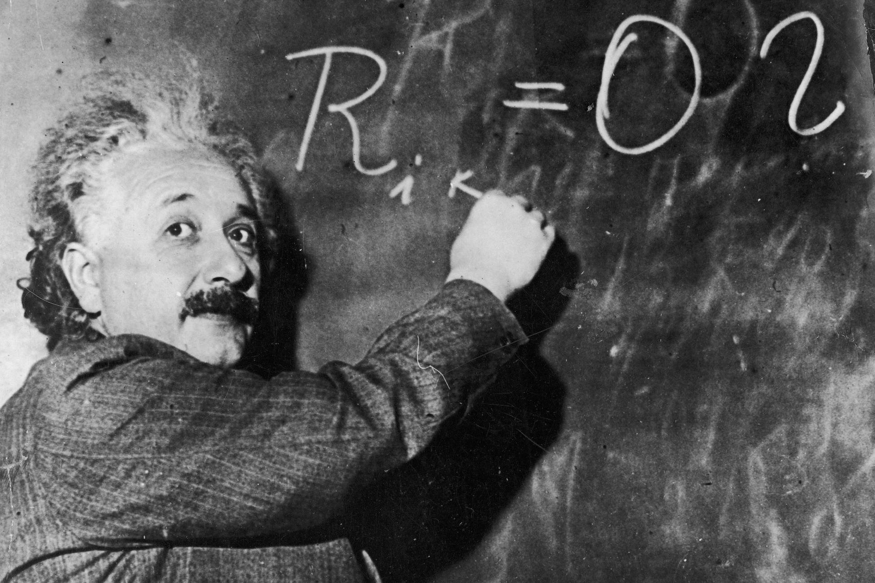 Albert Einstein writing a formula on the board